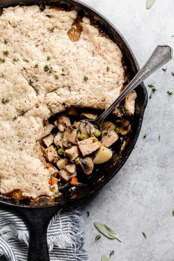 A spoon rests in a cast iron skillet where a servings of Paleo Turkey Pot Pie has been dished out.
