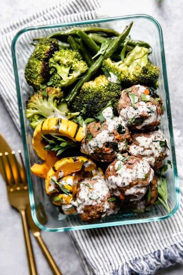 Rectangular glass dish filled with meatballs (drizzled with dressing), squash, broccoli and green beans resting on striped napkin with fork and knife on the side