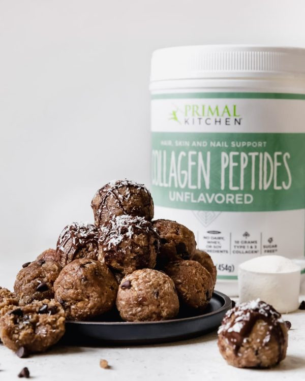Almond Joy Protein Bites, made with Primal Kitchen Collagen Peptides, are stacked on a plate.
