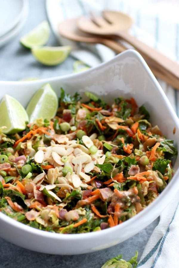 White bowl filled with chopped salad with brussels sprouts, carrots, bacon, almonds and golden raisins with lime wedges on side