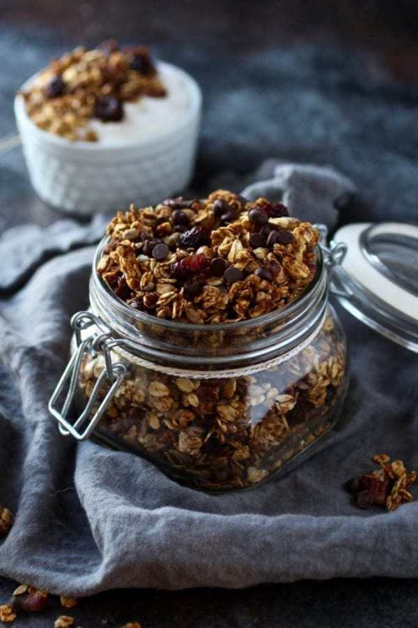 Small canning jar filled with granola surrounded by cloth napkin and a cup of yogurt with granola in the background