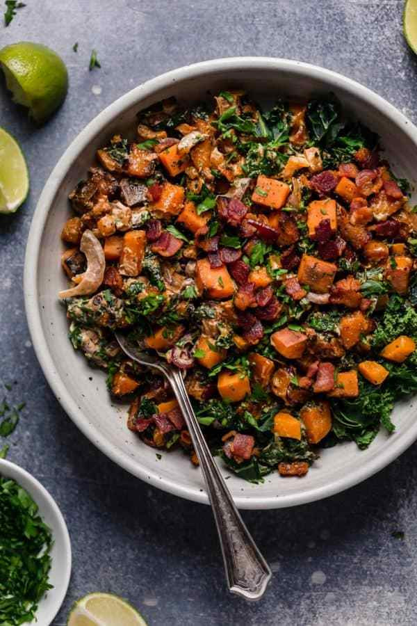 warm chipotle lime sweet potato salad in a bowl with spoon and lime garnish surrounding.
