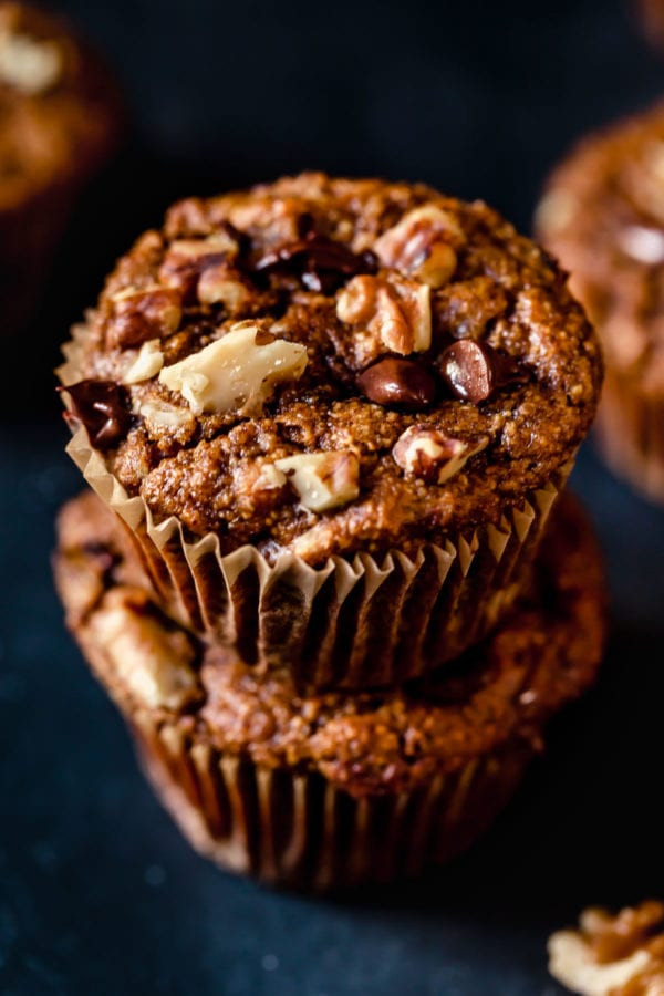 Close up of two Grain-Free Sweet Potato Banana Nut Muffins stacked on top of one another (with chocolate chips and walnuts on top).