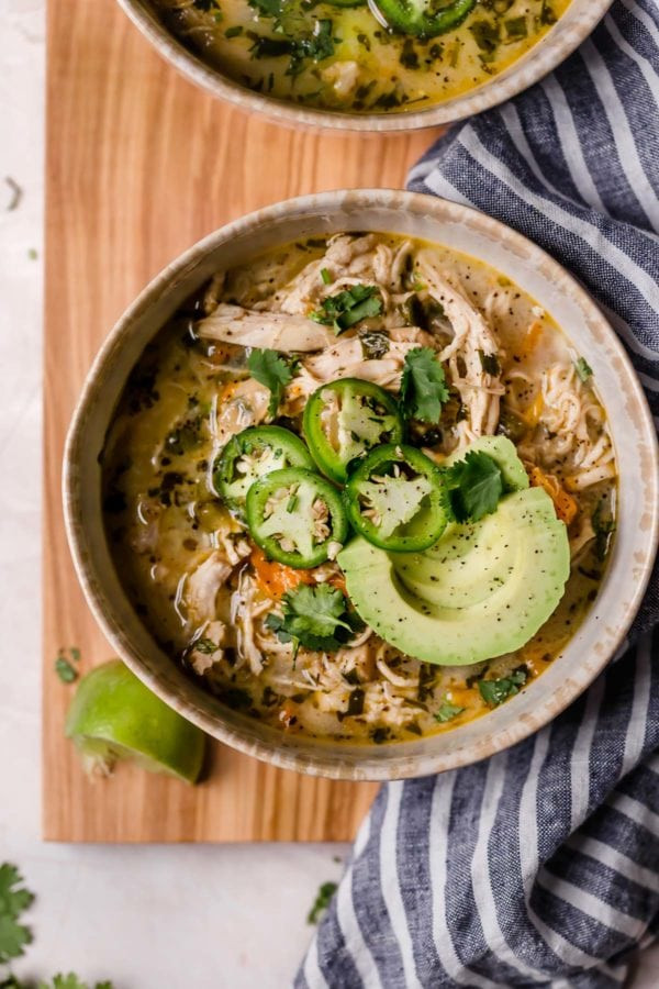 Bowl of white chicken chili with jalapeño and avocado garnish, resting on a wooden cutting board with a striped napkin surrounding it
