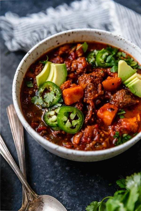 A close up shot of a white bowl on a dark surface that's filled with Slow Cooker Chunky Beef Chili with Sweet Potatoes and topped with sliced jalapeños, avocado, and fresh cilantro.