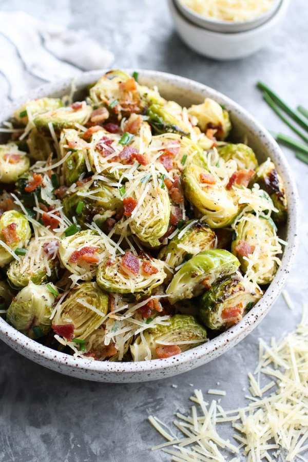 Bowl filled with roasted Brussels sprouts covered in parmesan and bacon pieces with bits of parmesan and green onion surrounding it. Part of the 12 Healthy Thanksgiving Side Dish Recipes.
