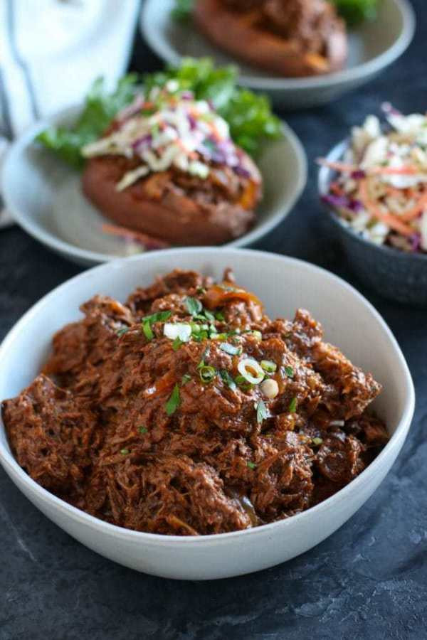 White bowl of bbq shredded beef garnished with onions. With plated bbq beef stuffed sweet potato in background