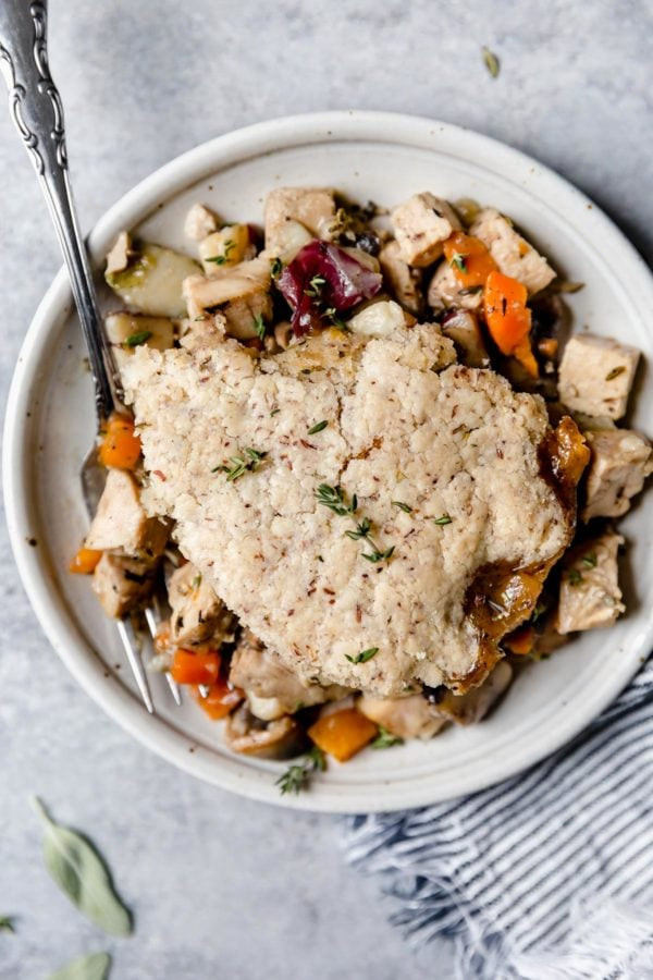 A overhead view of a plate of turkey and vegetables in a thyme-sage gravy is topped with a flaky grain-free pastry crust in this Paleo Turkey Pot Pie.
