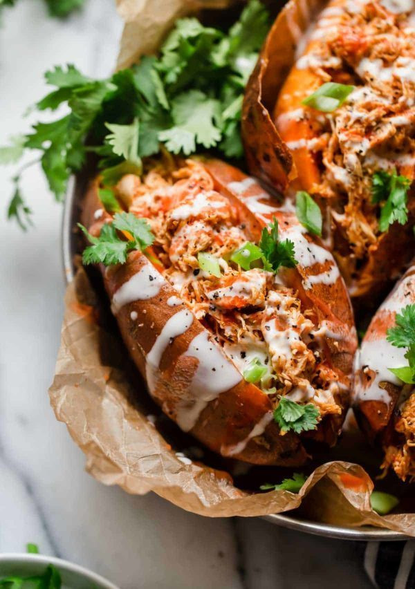 sweet potatoes stuffed with buffalo chicken with green onion.