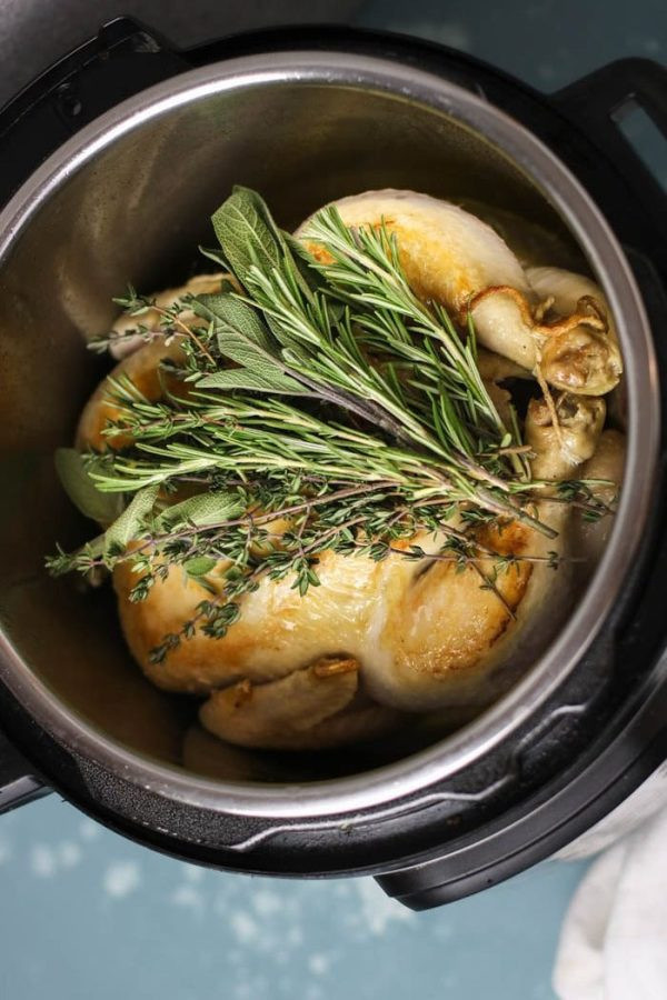 Whole chicken in an Instant Pot with herbs on top.