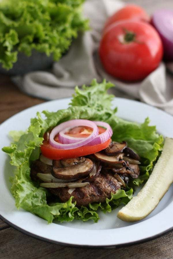 Grilled burger topped with mushroom, tomato and onions and wrapped in lettuce leaf on a white plate with a pickle spear on the side.