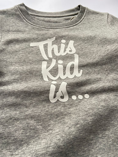"""Grey Marl Sweater with white screen print logo in serif font """"This Kid Is"""""""