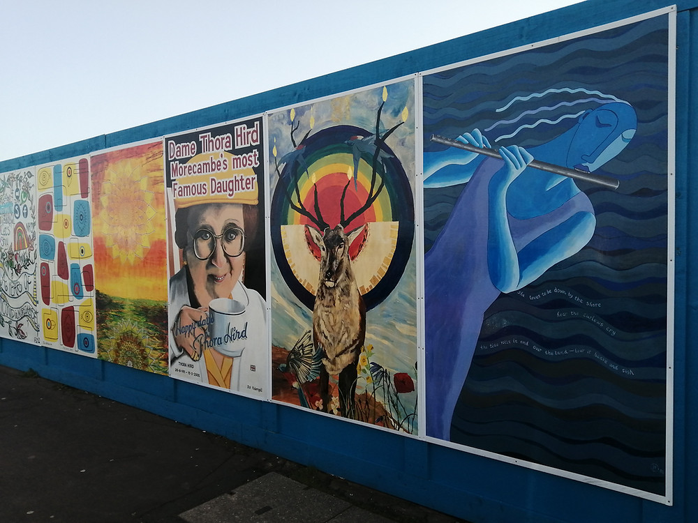 Picture of an 8 ft, blue fence slanting away to the left. With 6 large paintings on, covering most of the fence. Each painting is different. The painting closest is of a slightly abstract blue lady, playing the flute in front of the sea. Next to the lady is a different painting of a deer, the tips of its antlers are on fire, with two swallows flying between them, there are concentric circles behind the deer, red in the centre, then orange, yellow, green, turquoise then dark blue. The third painting depicts Actress Thora Hird, dressed as a tea lady, with 'Dame Thora Hird Morecambe's most famous daughter' written above her.
