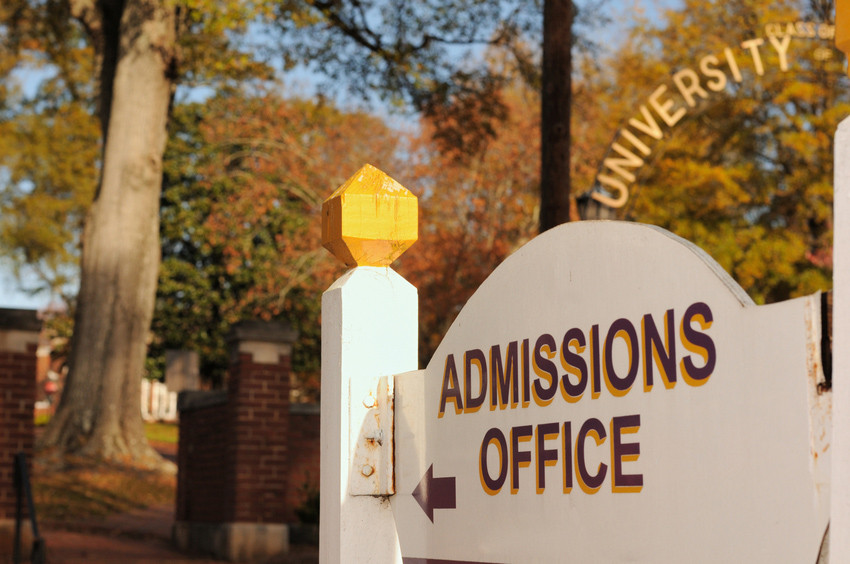 Directional sign for admissions office under arched university sign