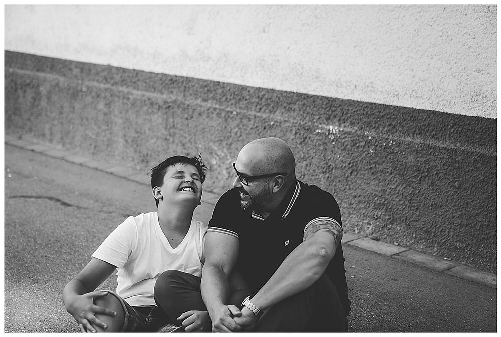lachendes Kind sitz mit Papa auf dem Boden