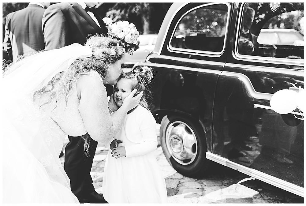 Braut küsst Tochter auf Stirn vor dem Hochzeitoldtimer in Ammersbek