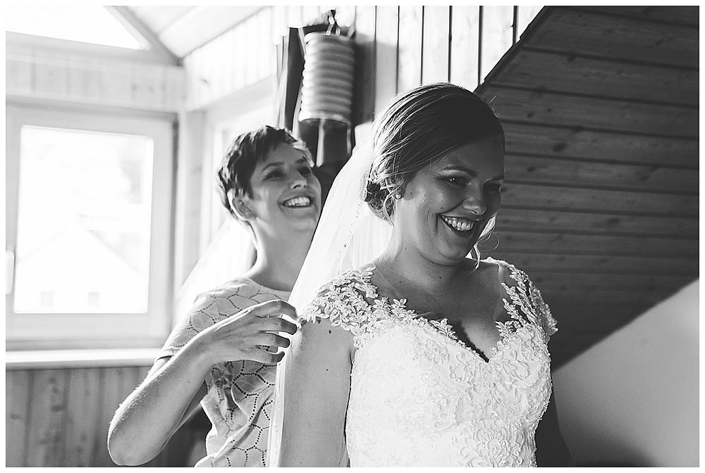 Braut und Schwester beim Kleid anziehen Hochzeit