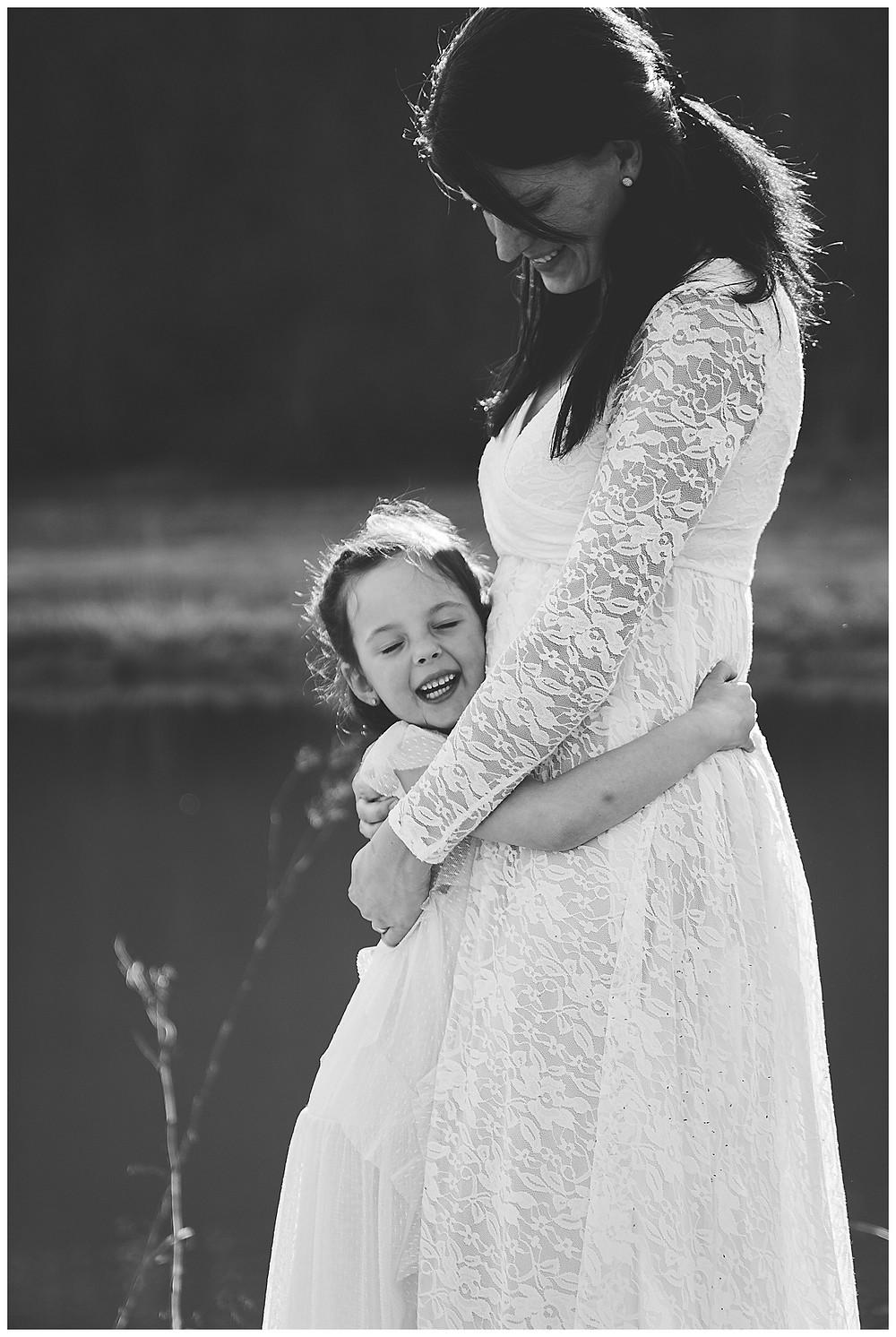Mama umarmt Kind bei Sonnenschein