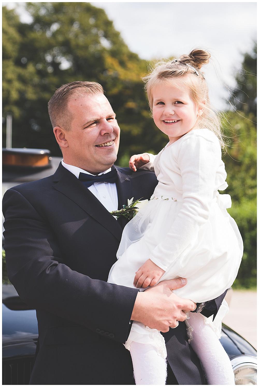 Bräutigam hebt Tochter hoch