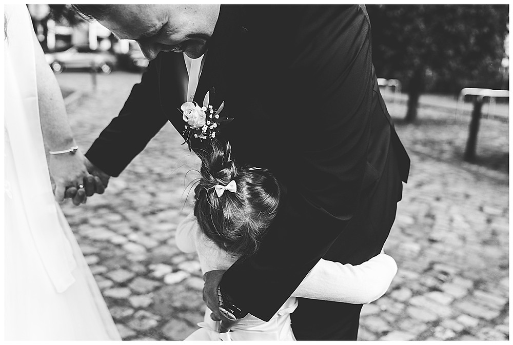 Bräutigam umarmt Tochter vor Standesamt
