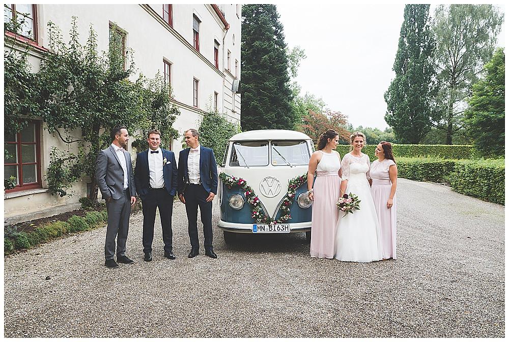 Hochzeitspaar mit Trauzeugen vor dem Bulli