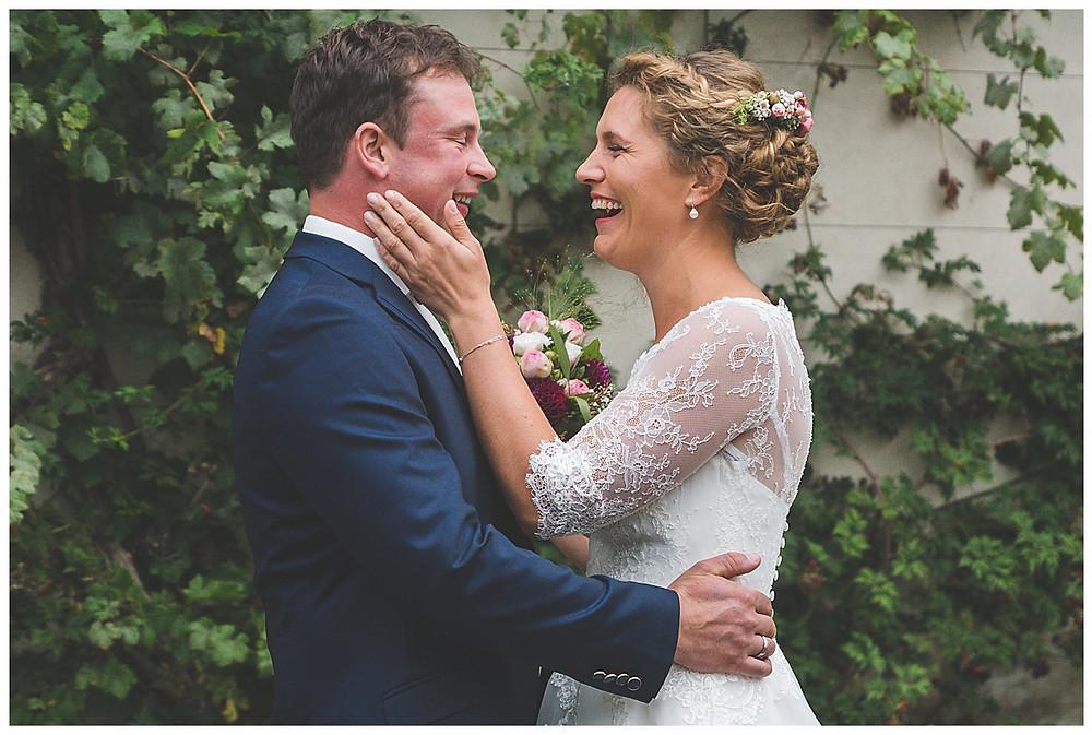 Braut streichelt Bräutigam über die Wange beide lachen