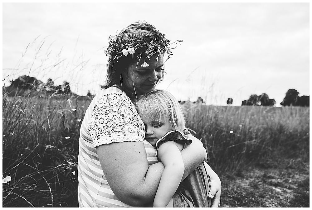 mama kuschelt mit Tochter in Blumenwiese