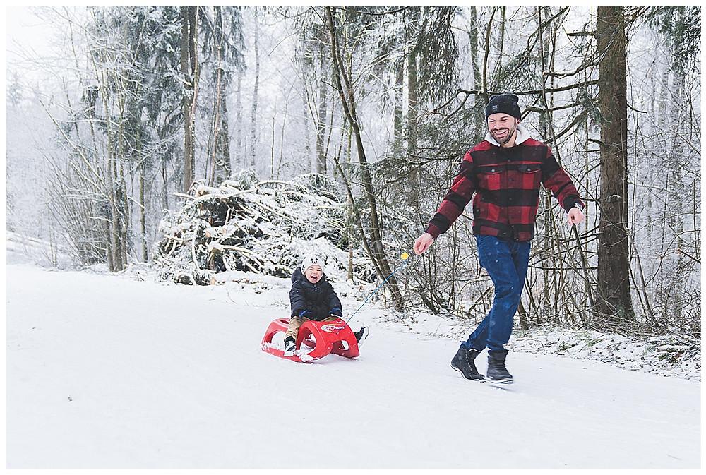Papa zieht Kind im Schnee auf Schlitten