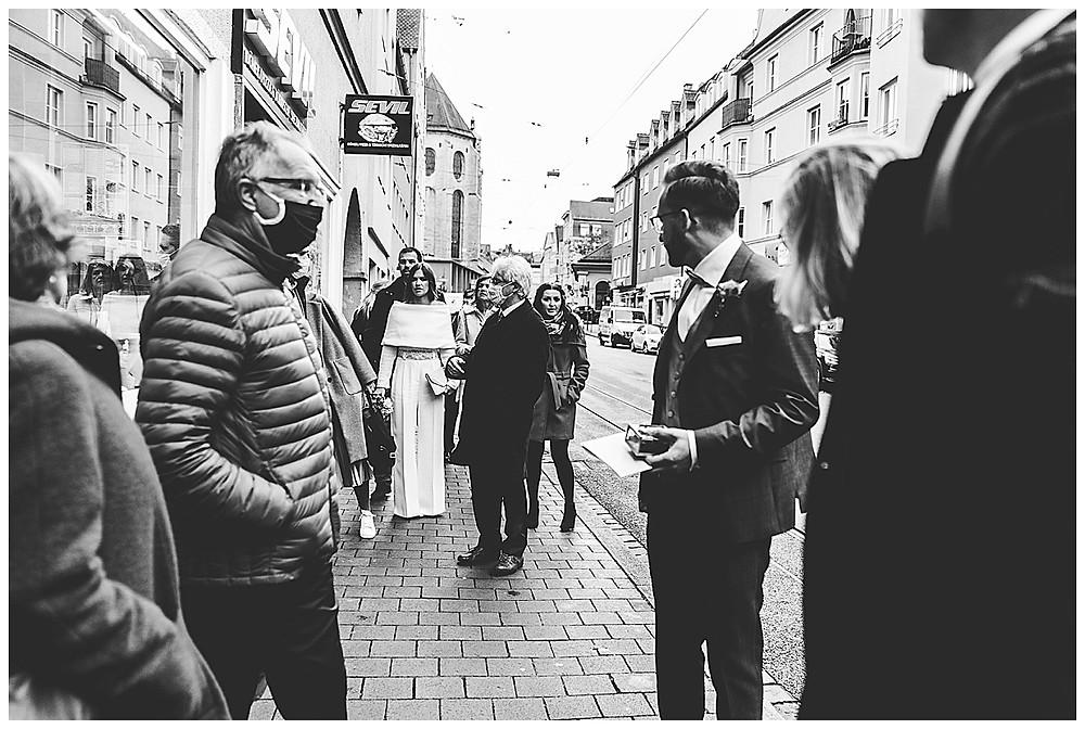 Hochzeitsgesellschaft läuft durch Stadt