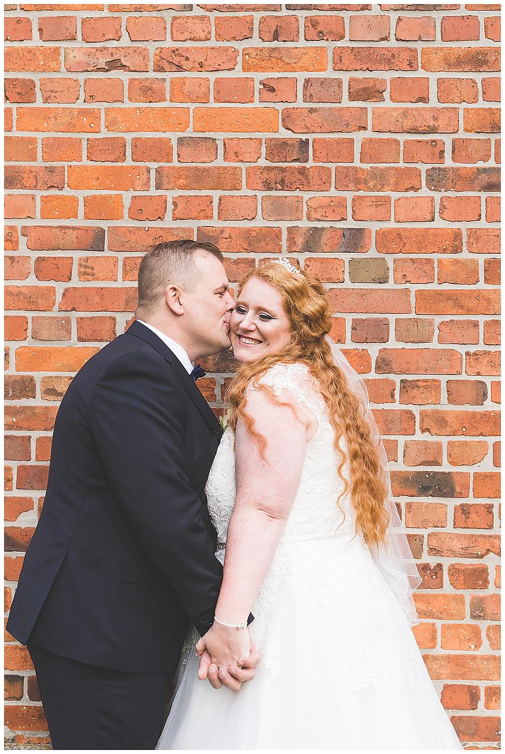 Bräutigam küsst Braut auf Wange Händchen haltend