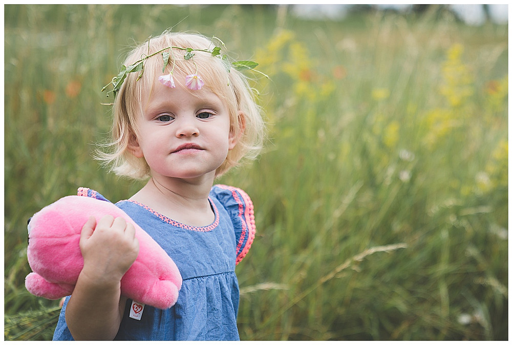 blondes Kind mit Blumenkranz im haar