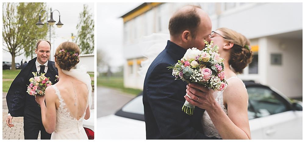 Brautpaar vor Location stehen und küssen sich