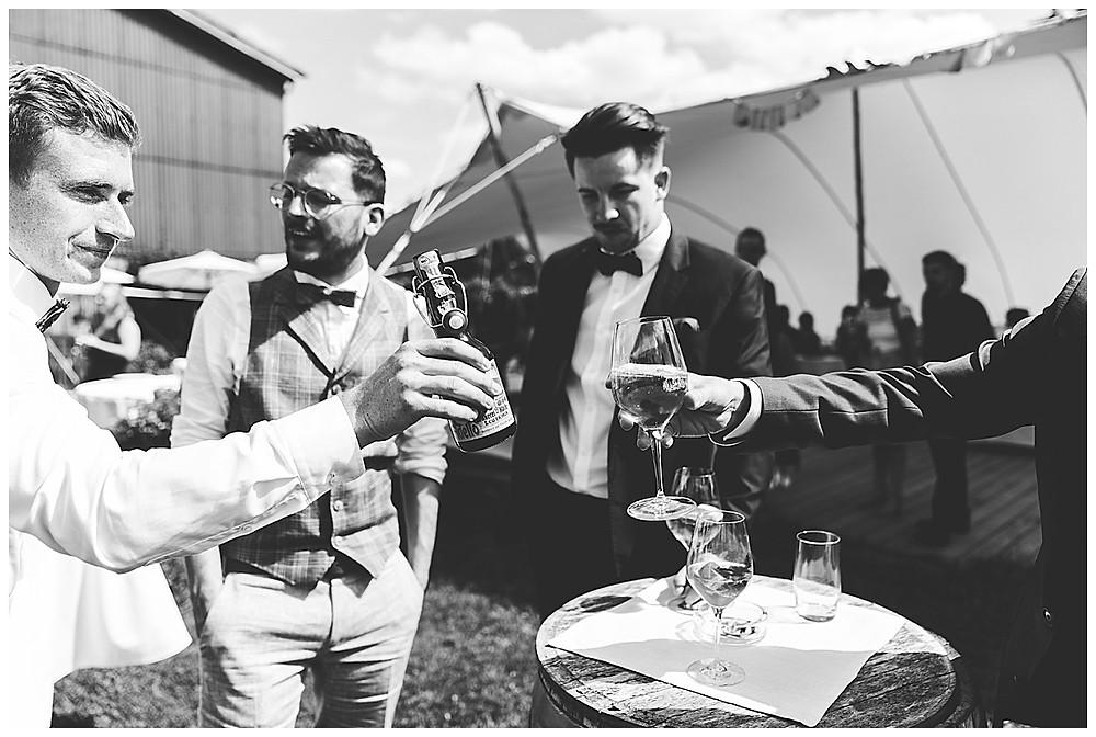 Männer stoßen mit Bier an auf Hochzeit