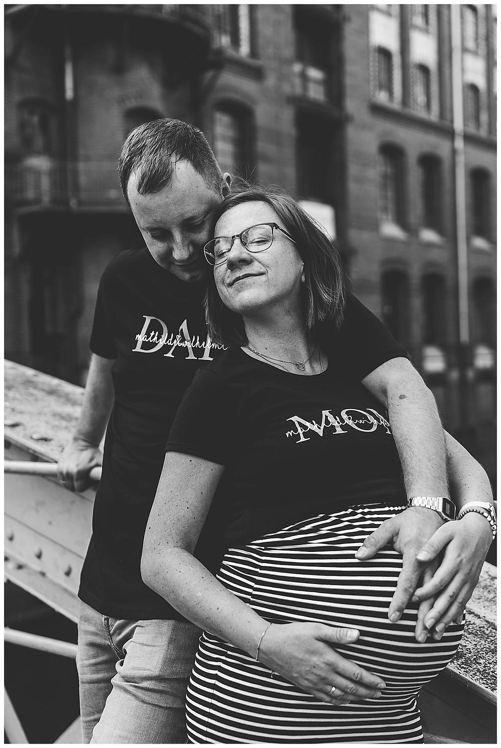 schwangere kuschelt an ihren Mann in Speicherstadt Babybauchshoot