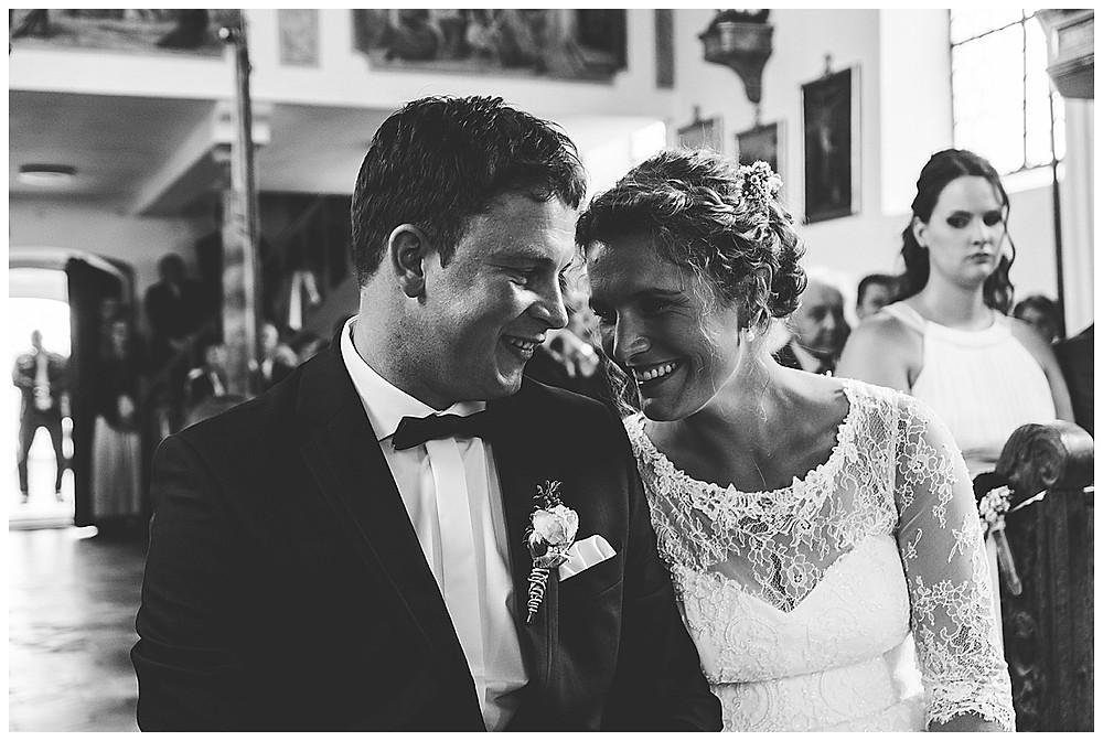 Brautpaar sitzend in der Kirche lachend  küssend