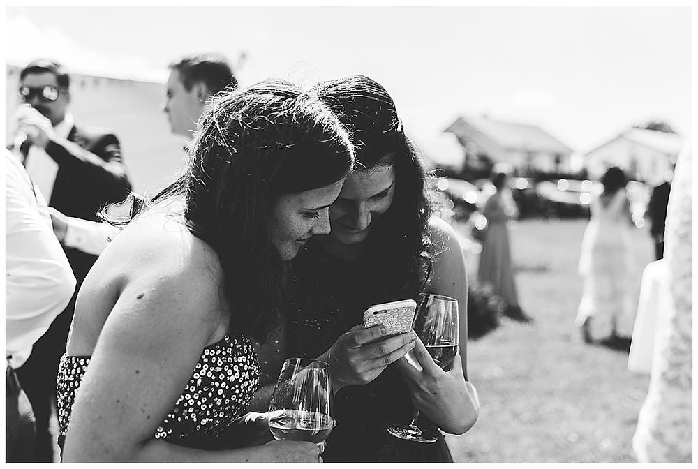 Gäste bei Hochzeit schauen in Handy