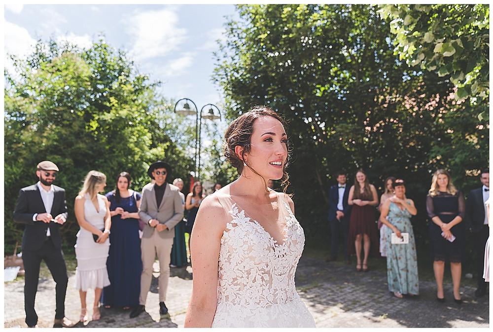 Braut steht im Kreis bei ihren Freunden