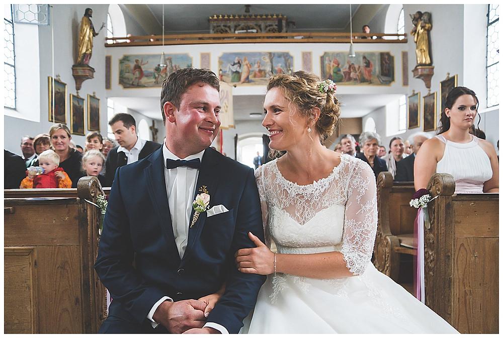 Brautpaar sitzend in der Kirche lachend