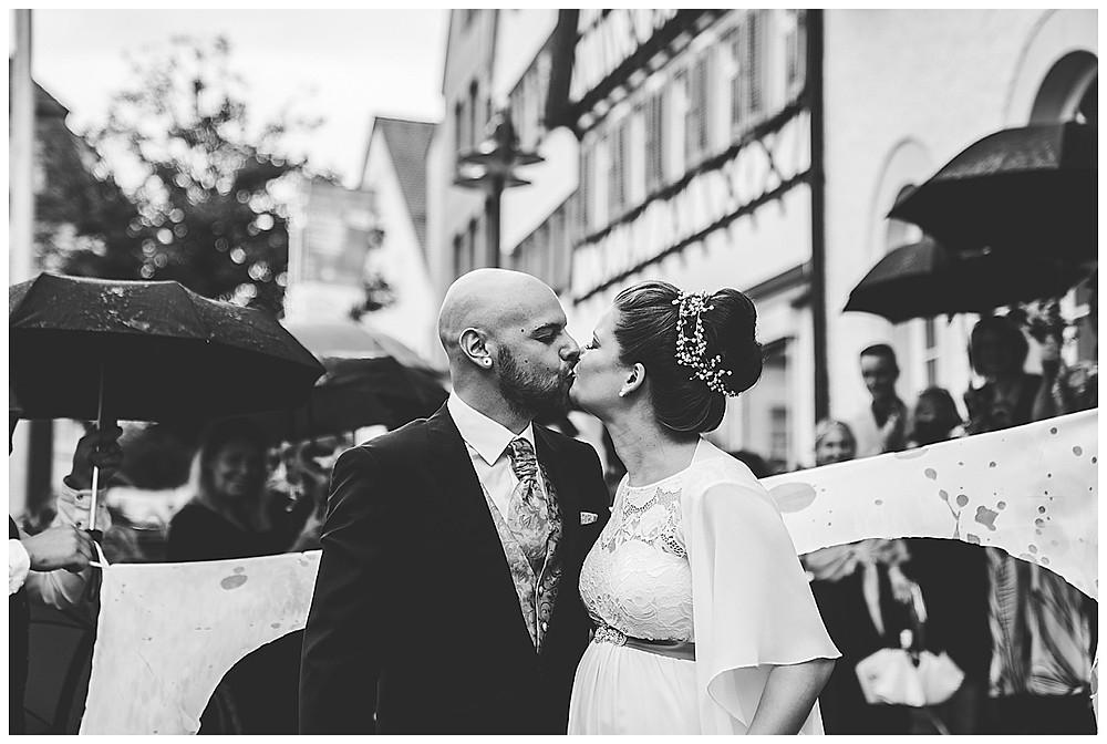 Brautpaar küsst sich vor Standesamt