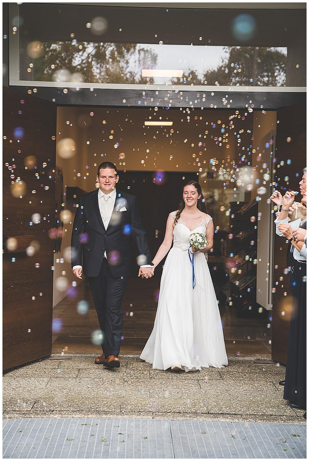 Seifenblasen und Brautpaar vor Kirche