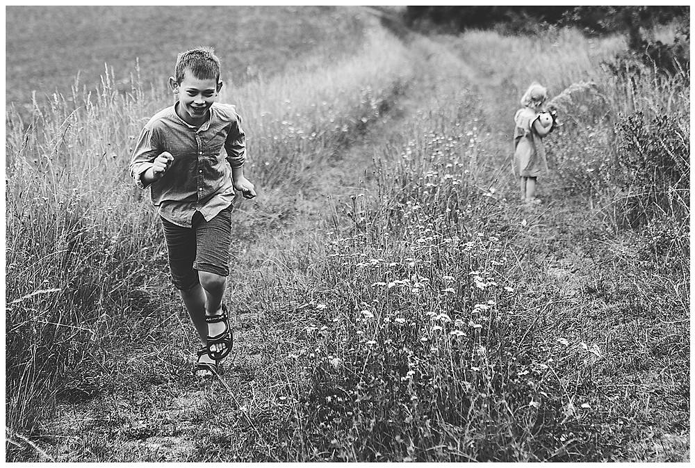 Bub rennt über Feldweg, schwester pflückt Blumen