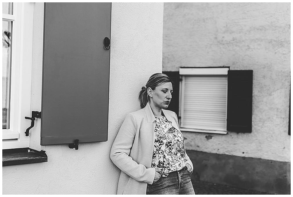 Frau lehnt an Wand