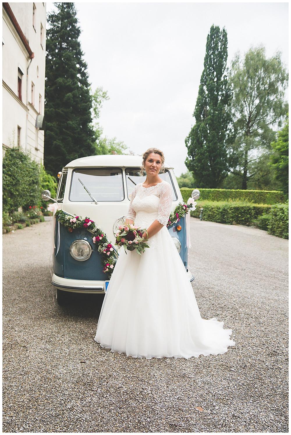 Braut steht vor Brautauto VW Bully mit Straußen in der Hand
