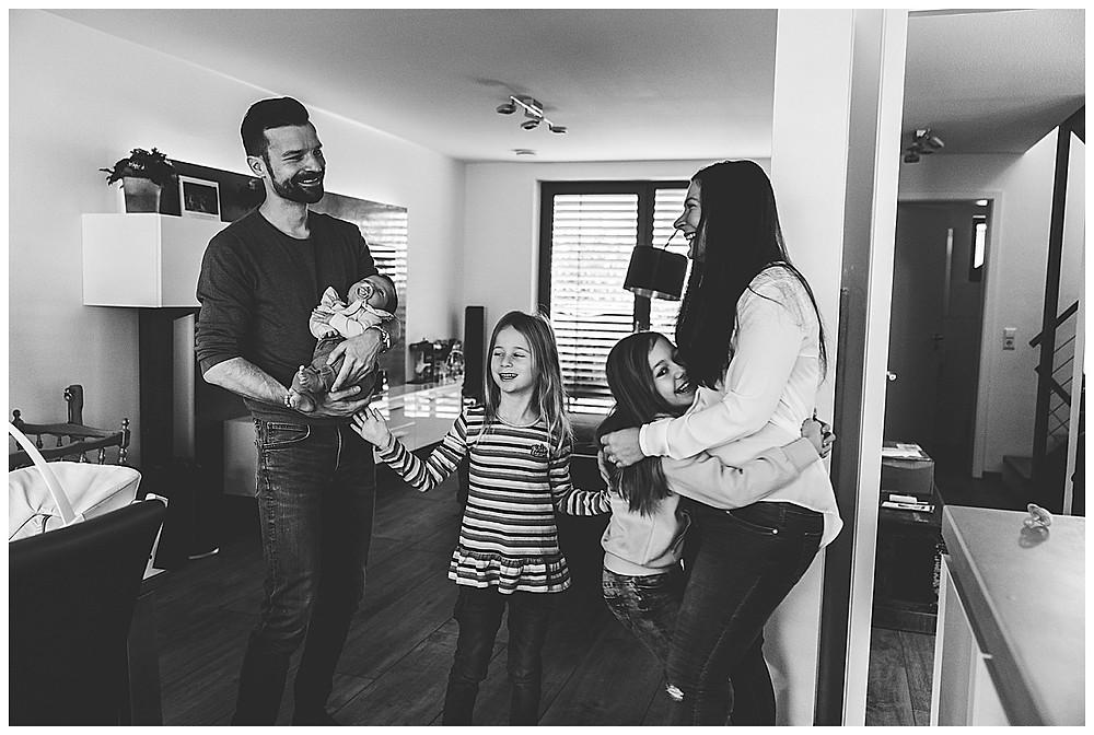 Familie lacht bei Babyreportage zuhause