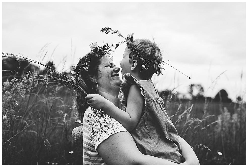 Kind sitzt auf Mama und schleckt ihr übers Gesicht