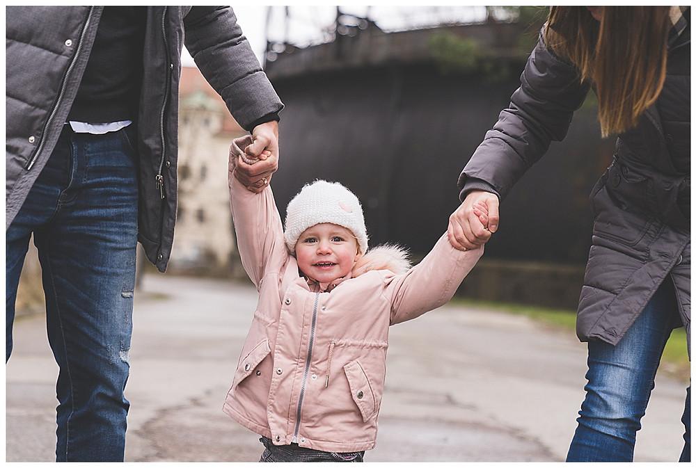 Mama und Papa halten Kind fest Fotograf Augsburg
