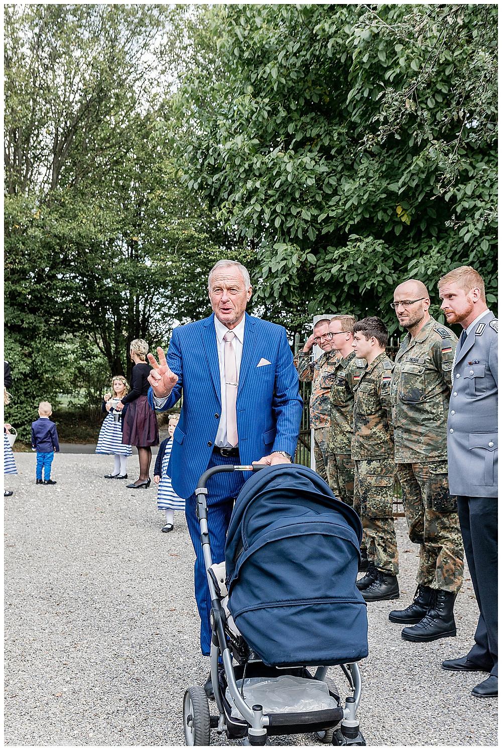 Mann mit Kinderwagen auf Hochzeit