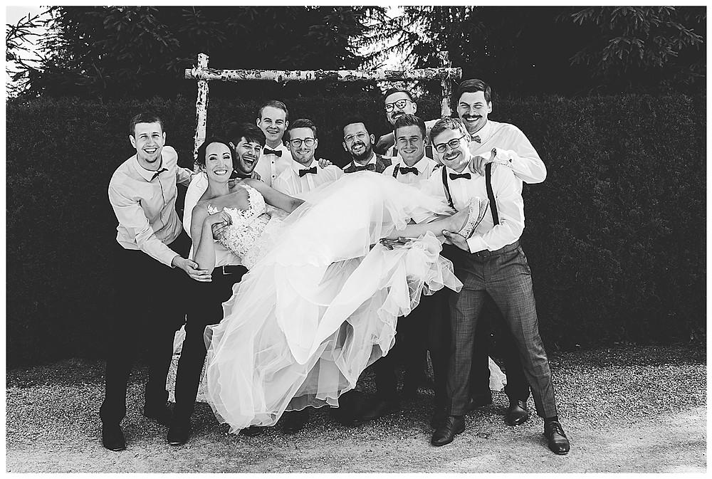 Männliche Gäste heben Braut hoch