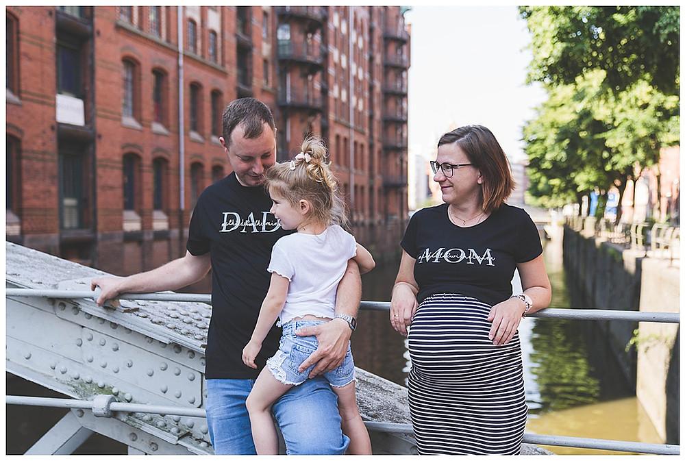 Familienshooting in Hamburg Kind sitzt auf Papa schwangere Mama schaut zu ihnen