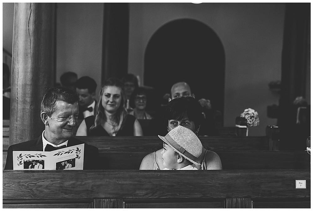 Brautpapa lächelt Enkel zu in Kirche